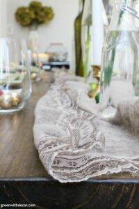 A simple Christmas centerpiece + tablescape with wine bottles, flowers, candles and little ornaments. This looks easy to put together and I love that she used a scarf as a table runner - so easy!