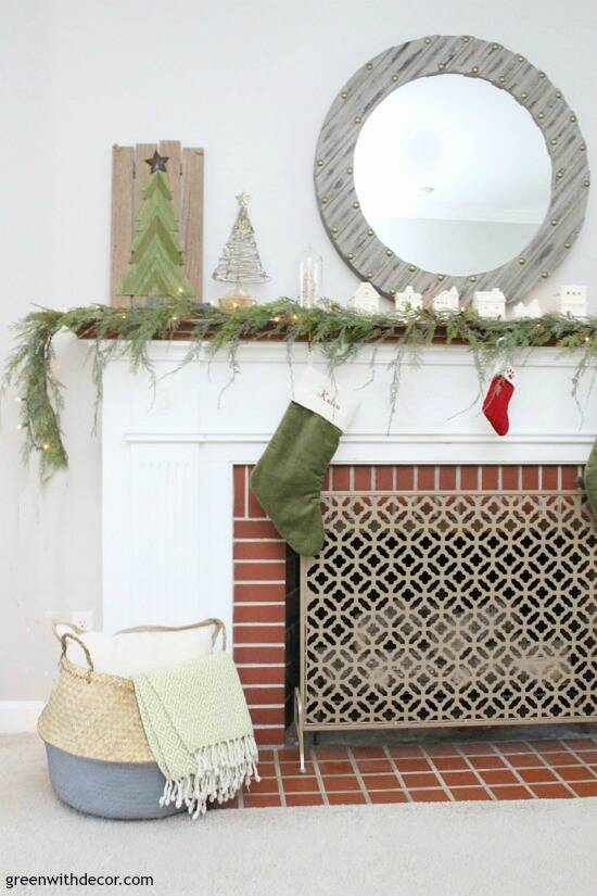 A simple Christmas mantel with village pieces and pretty faux garland, plus that gorgeous seagrass basket!