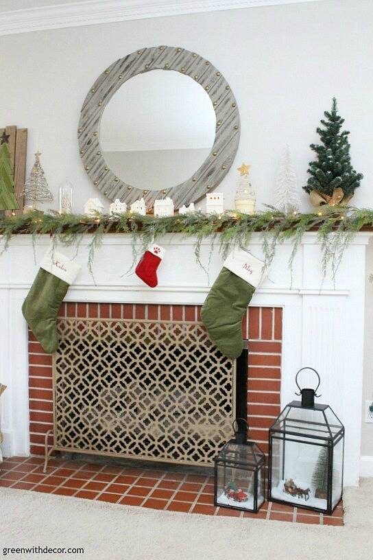 A simple Christmas mantel with village pieces, that faux garland looks real - I love it with the mini Christmas trees and the white Christmas lights!