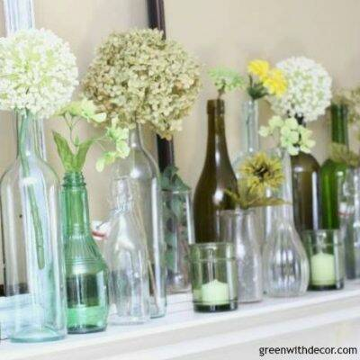 An easy spring mantel decorating idea with old glass bottles and wine glasses. This is so pretty and would be easy to put together!