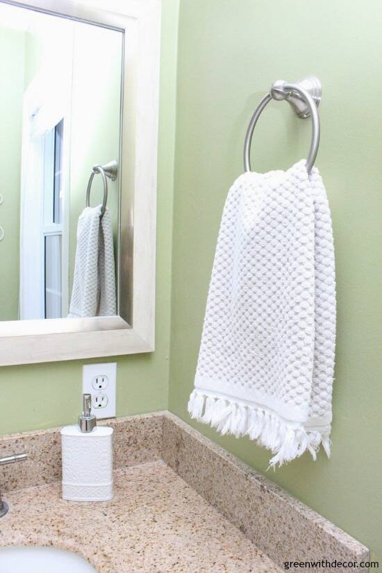 You don't have to spend a lot to update a bathroom - this bathroom makeover cost just $100! She made easy changes - painting the walls, new vanity hardware, new mirror and other easy DIY fixes!