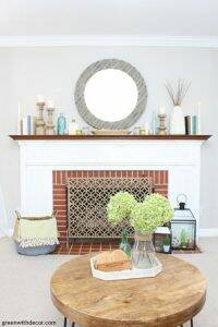 A simple coastal mantel using wood candlesticks, books and glass vases