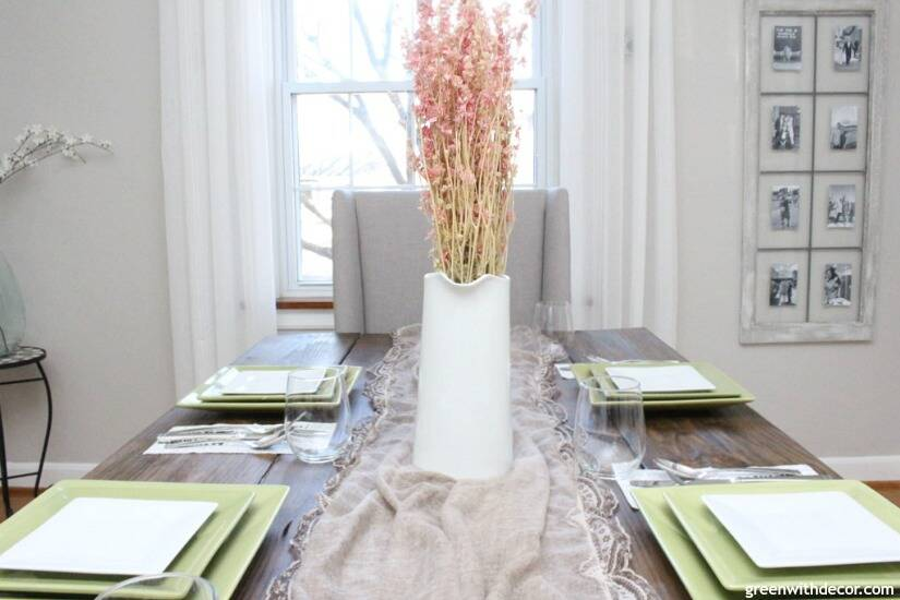 An easy Valentine's Day centerpiece and tablescape with a pretty lace scarf as a table runner and pink flowers in a white pitcher.