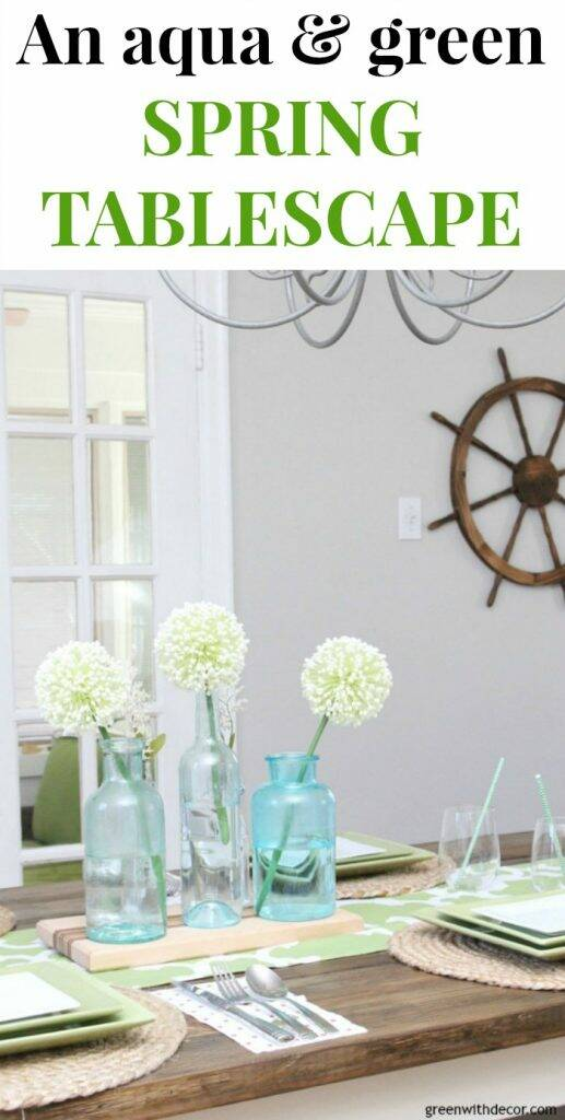 An easy aqua and green coastal tablescape - perfect for a spring brunch or Easter dinner! Love the pretty glass clear and aqua bottles for a centerpiece - they look great on top of that wood cutting board. And that table runner is actually a window valance - genius upcycle! Love the ship wheel on the wall, too, perfect for a coastal dining room!