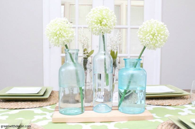 An easy aqua and green coastal tablescape - perfect for a spring dinner or Easter brunch! These aqua glass bottles are perfect for a spring centerpiece - love them with the white flowers sitting on the wood cutting board!
