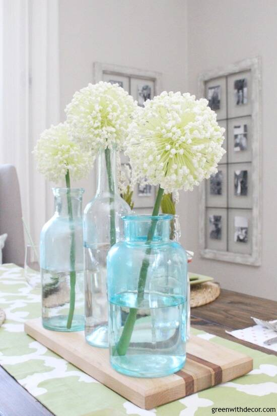 An easy aqua and green coastal tablescape - perfect for a spring dinner or Easter brunch! These aqua glass bottles are perfect for a spring centerpiece - love them with the pretty white flowers on top of the wood cutting board!