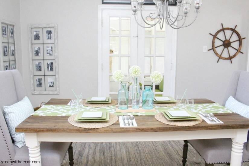 An easy aqua and green coastal tablescape - perfect for a spring dinner or Easter brunch! The farmhouse table looks great with the green and white table runner and aqua glass bottles as a centerpiece. Love that ship wheel on the wall, too!