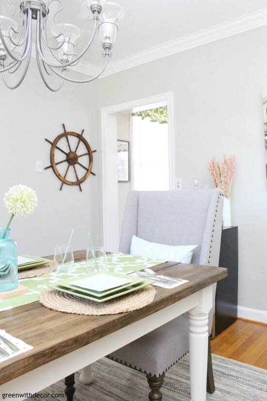 A dark wood farmhouse dining table with white legs, a gray fabric chair at the end, gray walls with a wooden ship wheel.