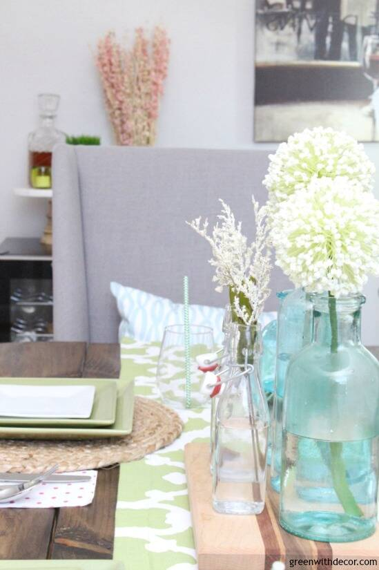 An easy aqua and green coastal tablescape - perfect for a spring dinner or Easter brunch! These aqua glass bottles are perfect for a spring centerpiece - love them with the pretty white flowers sitting on the wood cutting board!