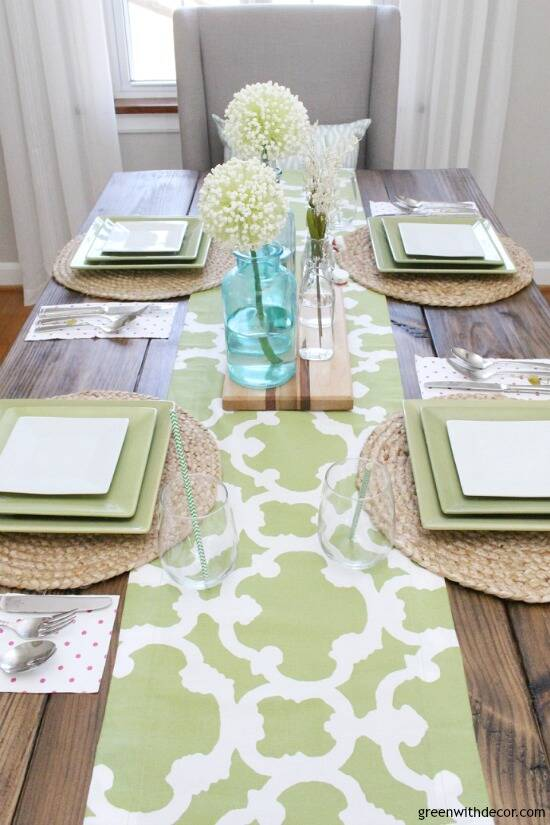 An easy aqua and green coastal tablescape - perfect for a spring dinner or Easter brunch! The farmhouse table looks great with the green and white table runner - would you believe it's actually a window valance? Such a good reuse for an old valance!