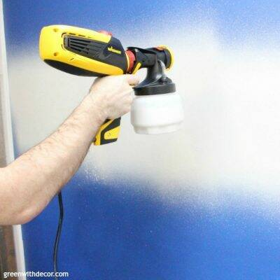Paint sprayer spraying a blue wall