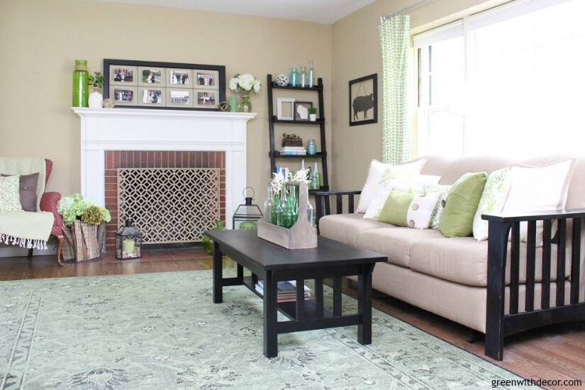 A pretty neutral tan paint color - Sherwin Williams' Camelback. It looks great in this coastal living room, pairs so well with aqua and green decor accessories and that tan couch!