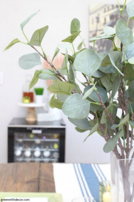 Faux eucalyptus with a wine fridge in the background