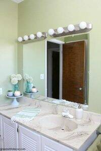Easy bathroom DIYs - hang mirrors vertically to make the room seem taller. So smart and easy!