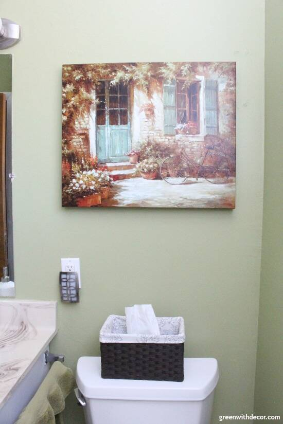Rental bathroom reveal - fun nightlight and baskets for tissues, and pretty green and brown artwork.