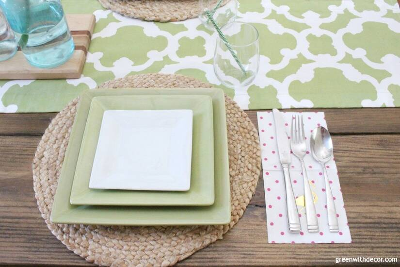 An easy aqua and green coastal tablescape - perfect for a spring dinner or Easter brunch! These jute chargers are perfect for a beachy, coastal table - love them with the green and white plates and those cute flamingo napkins!