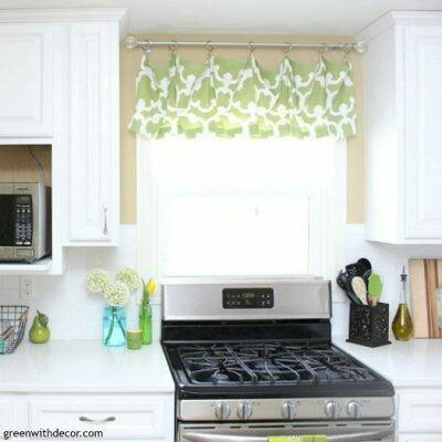 White kitchen with green and white window valance, stainless steel stove and white quartz counters