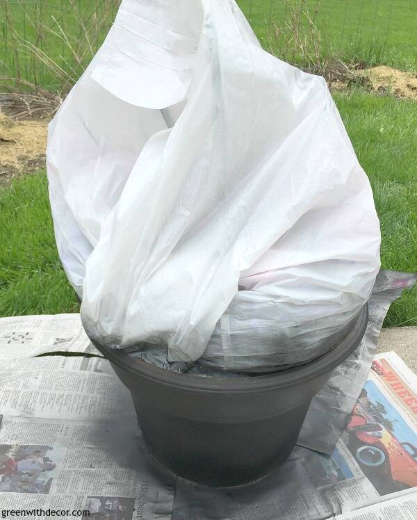 A spray painted plastic outdoor planter covered in plastic