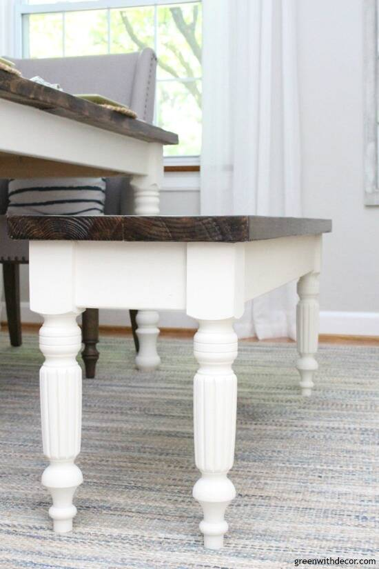 A farmhouse DIY bench with white legs and a dark wood top