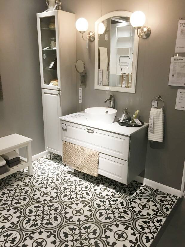 Bathroom with black and white tiled floor, gray vanity and white counter