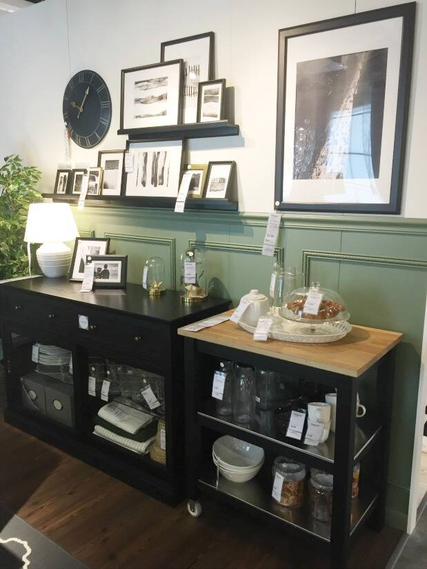 Green half wall with black shelving and black frames above