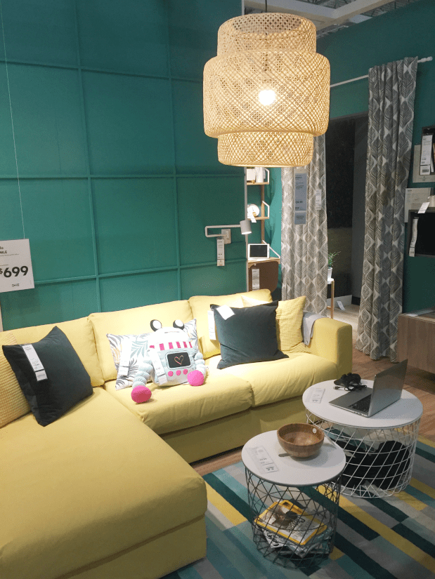 Boho light fixture in a room with dark teal walls and a yellow couch