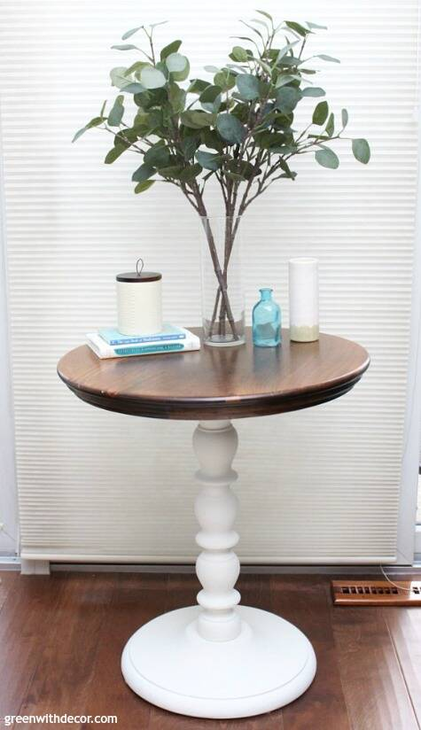 A two-toned round table with a white base and wood top with eucalyptus and white and aqua pieces on top