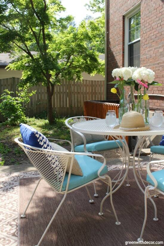 A tan metal patio set with aqua cushions, pillows and a flower centerpiece