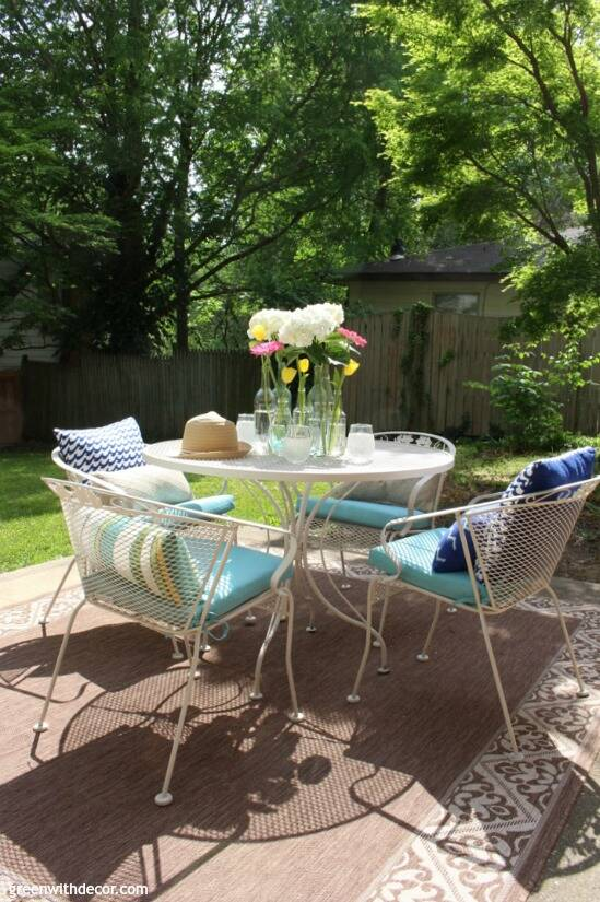 A tan metal patio set with aqua cushions, pillows and glass vases/flowers centerpiece.