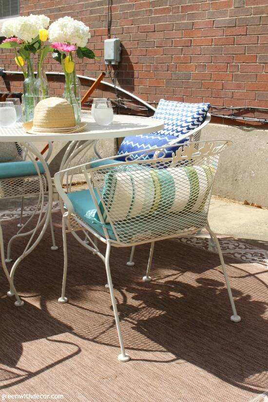 A tan metal patio table and chairs with aqua cushions, pillows and glass vases/flowers centerpiece.