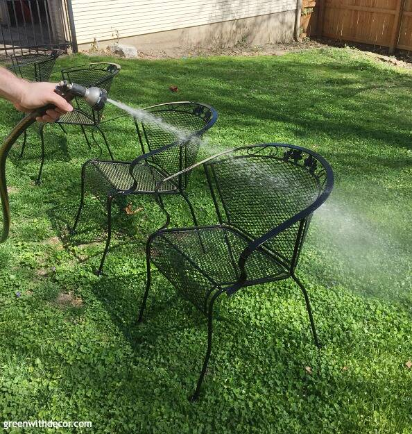Black outdoor metal chair beings prayed with a hose
