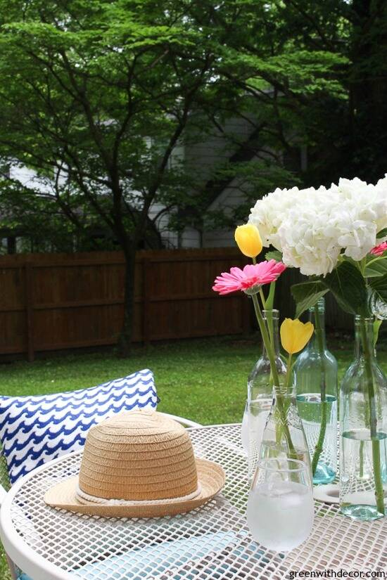 A blue and white patio with outdoor pillows, cushions, flowers and a plastic wine glass