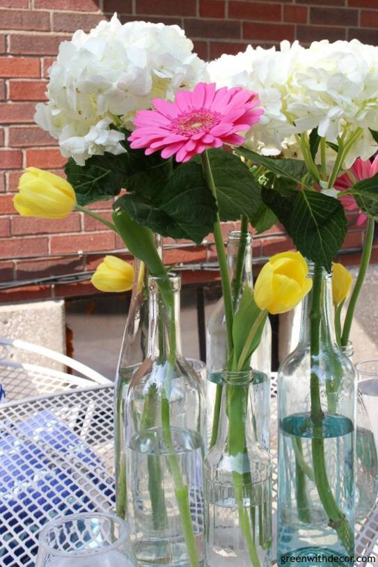 A blue and white patio with a glass bottle and flower summer centerpiece