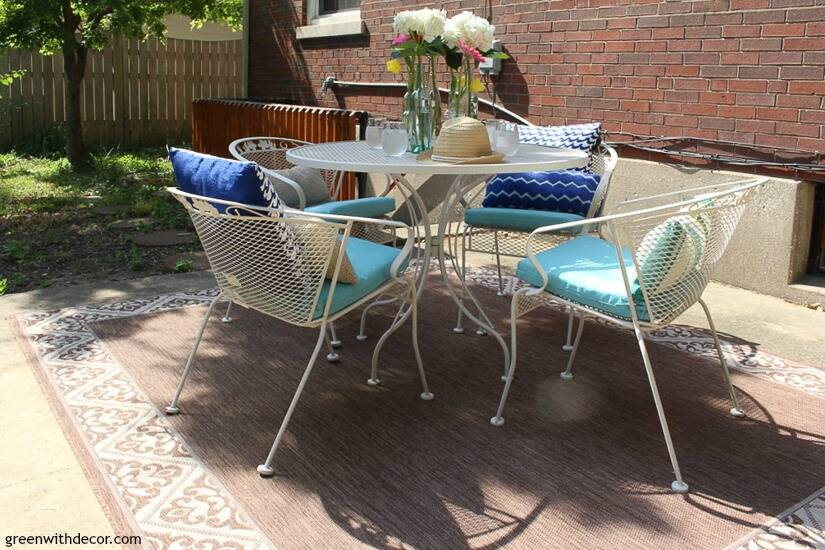 A blue and white patio with an outdoor rug, pillows, cushions and flowers.