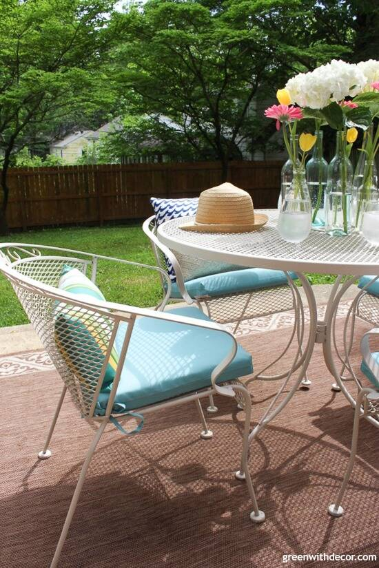 A blue and white patio with aqua pillows and cushions, flowers and a summer hat.