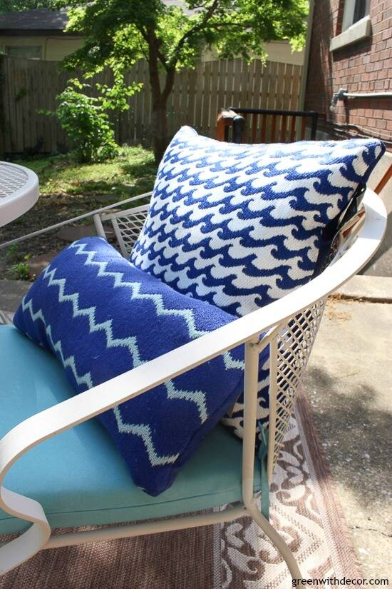 A blue and white patio with aqua cushions and blue outdoor pillows