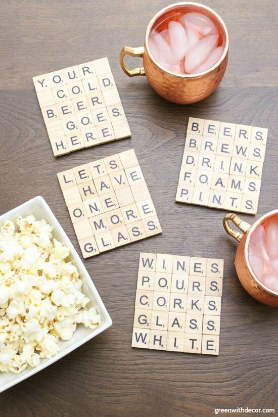 Scrabble tile DIY coasters near copper mugs and a white bowl of popcorn