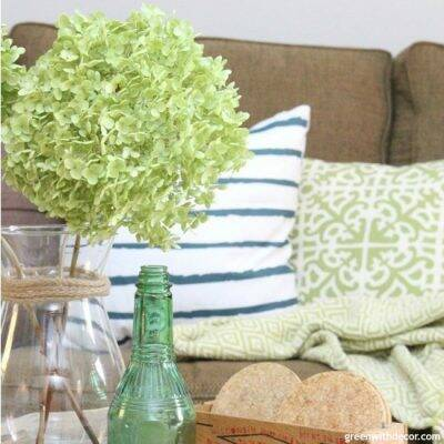 How to find your decorating style – a coastal living room with green hydrangeas and a striped pillow