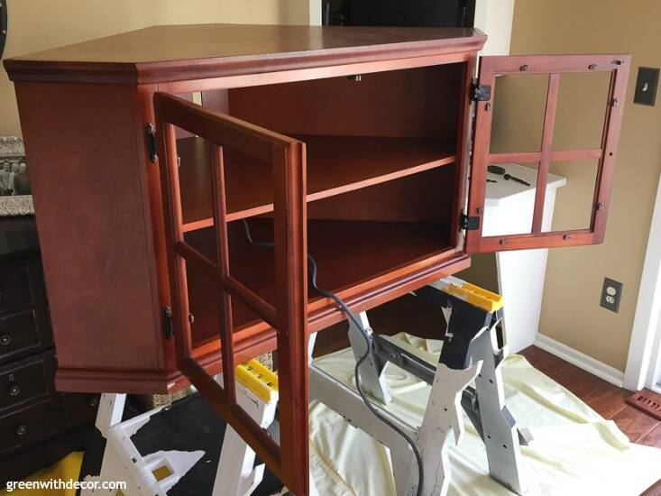 A brown wood TV stand before being painted