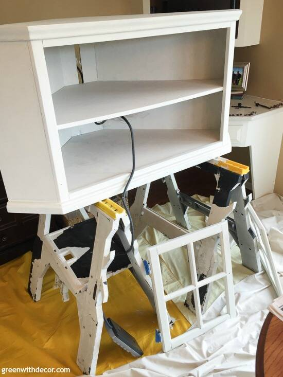 A brown wood TV stand being painted white with clay paint