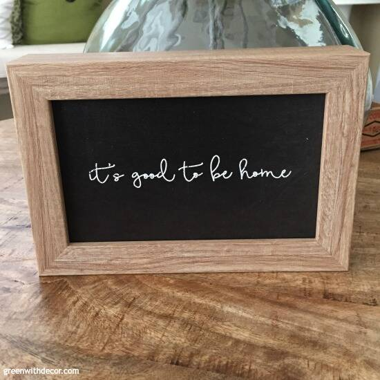 "Black and wood sign, ""It's good to be home"""