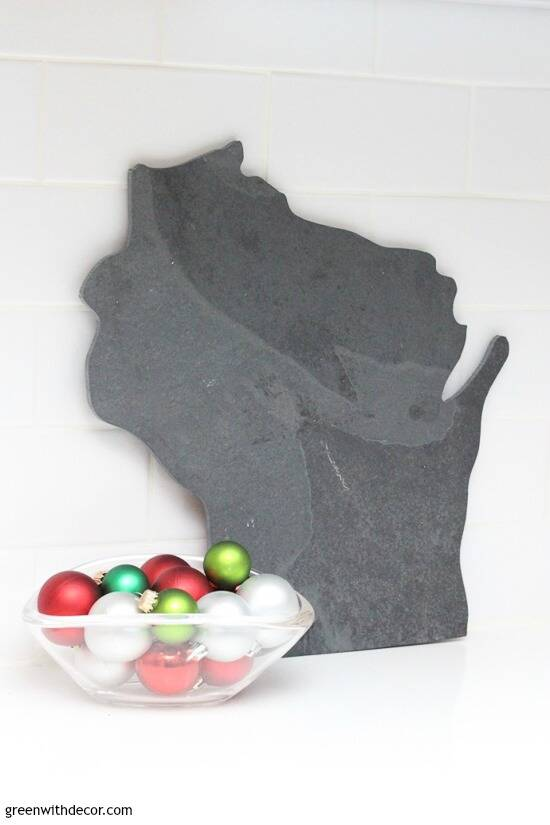 Wisconsin cutting board with clear glass bowl full of Christmas ornaments