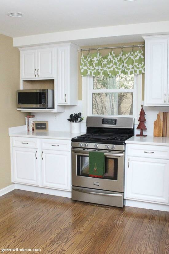 White kitchen with stainless steel stove decorated for Christmas