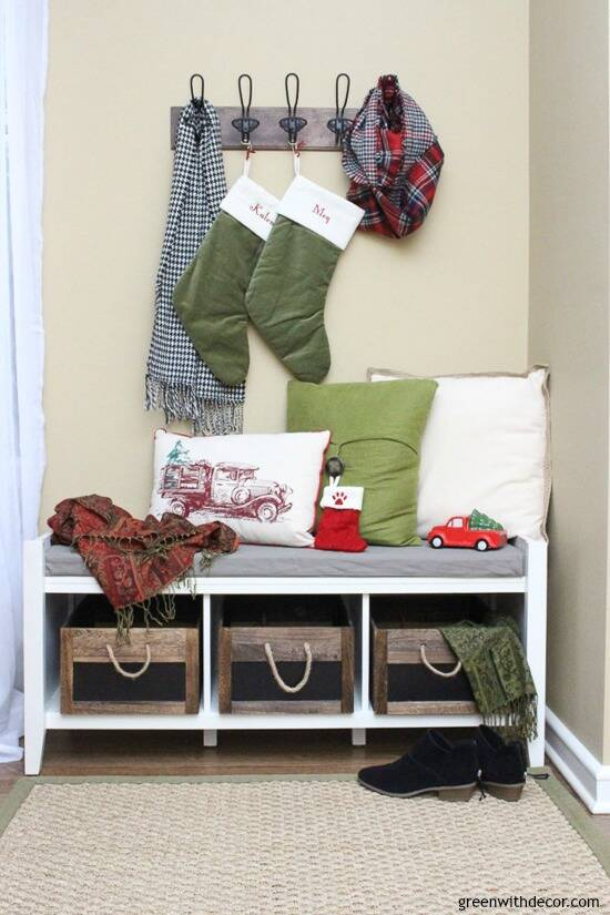 Christmas mudroom with green stockings, rustic crates and metal hooks