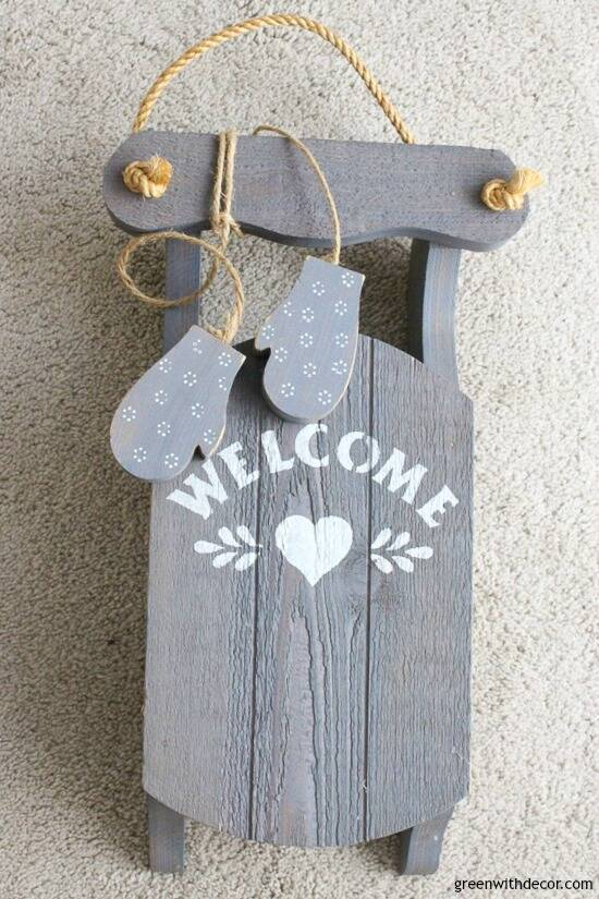 Outdated blue wood sled with 'welcome' written on it