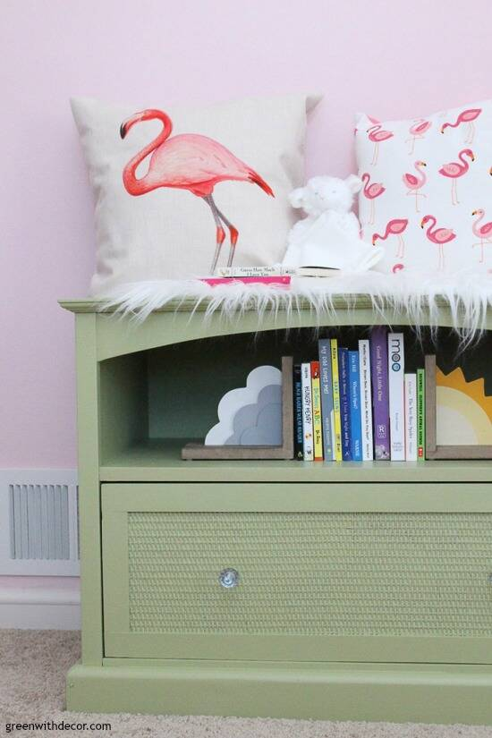 A green TV stand turned book storage for a nursery
