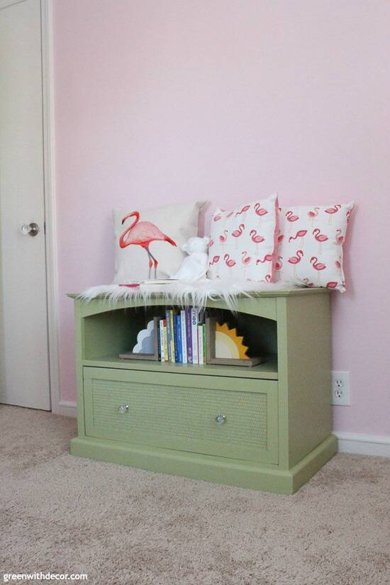 A green TV stand turned book storage in a girl's pink nursery