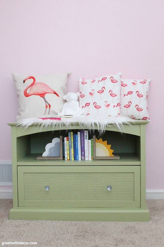 A green TV stand turned book storage in a pink nursery