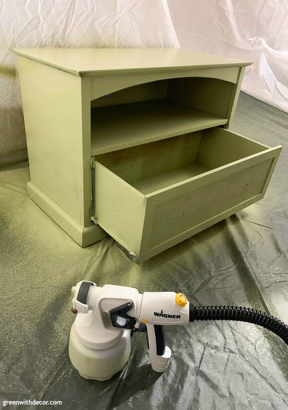 A Wagner Studio Pro paint sprayer sitting in front of a green painted TV stand