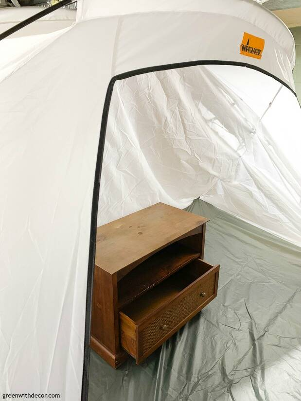 An old TV stand set up to be painted in a spray tent
